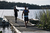 Young men carrying canoe away from lake