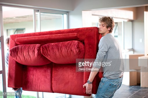 Young men carrying sofa