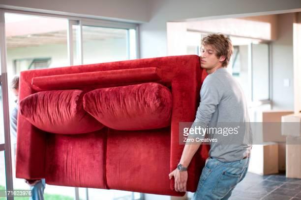 Young men carrying sofa