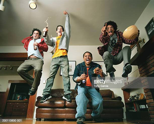 Young men cheering and jumping in air in living room, low angle view