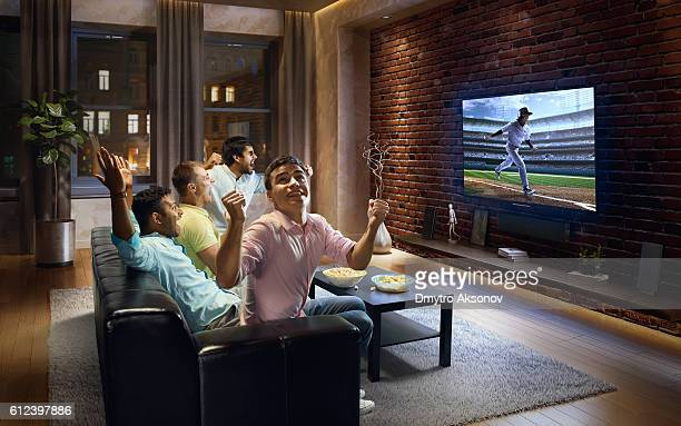 Young men cheering and watching Baseball game on TV