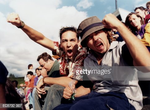 Young men cheering in stands during sporting event : Stock Photo