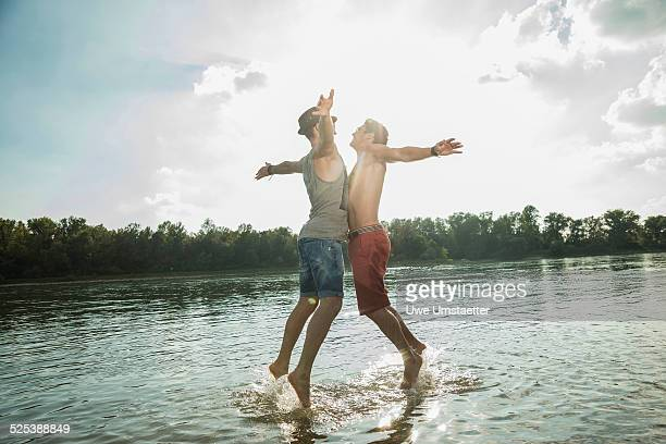Young men chest bumping in lake