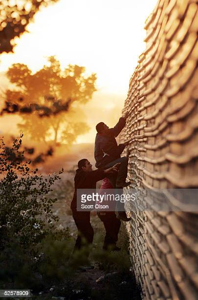 Young men climb a fence which divides the United States/Mexican border April 1 2005 in Agua Prieta Mexico More than 1000 volunteers from the...