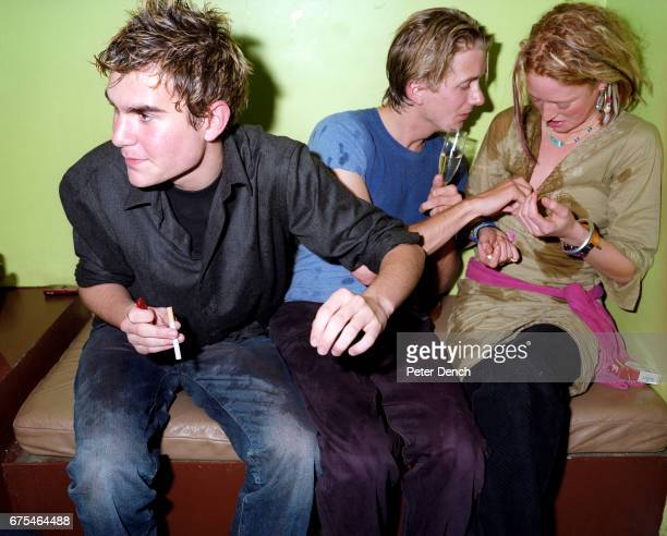 Young men drink with a woman in the basement of a private members bar in the upmarket Kings Road area of west London May 2000