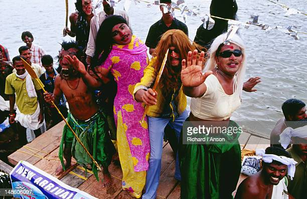 Young men entertaining spectators during pre-race procession on Pampa River River during Onam festival celebrations.