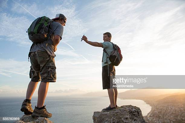 Young men exchange text message/photo at top of hike