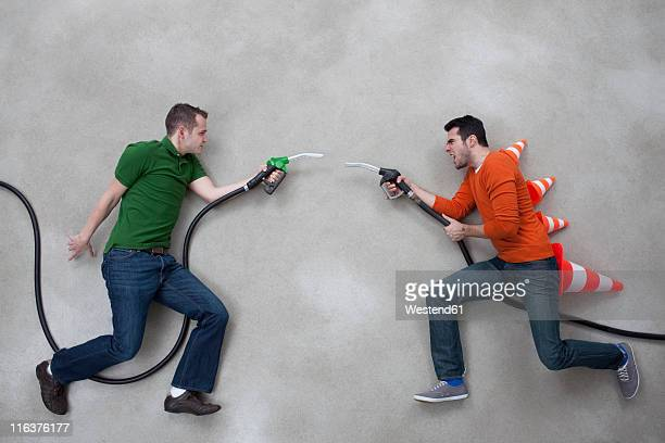 Young men fighting with fuel taps