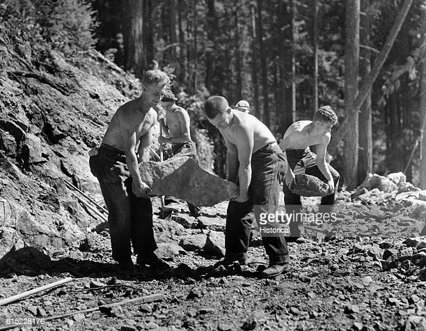 Young men from Camp F24 in the Civilian Conservation Corps clear rocks from a truck trail in Snoqualmie National Forest Washington   Location...