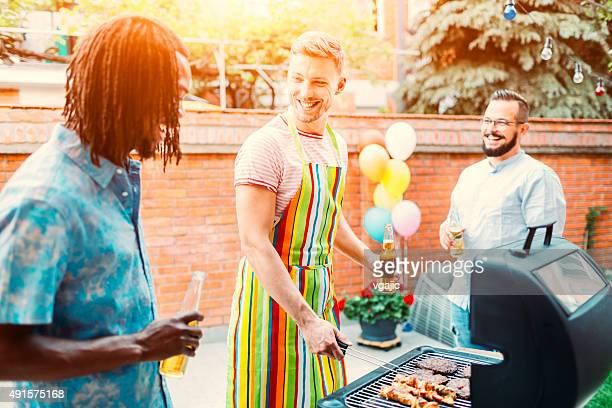 Young Men Grilling Meat At Barbecue Party.