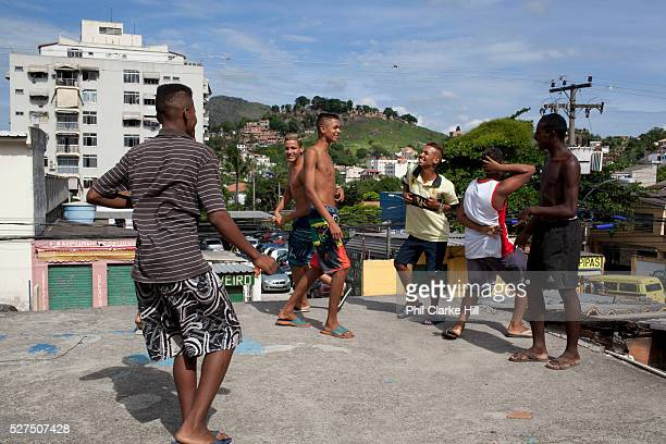 Young men guys on a rooftop with buildings in the background in Vila Valquiere West Zone Zona Oueste Rio de Janeiro
