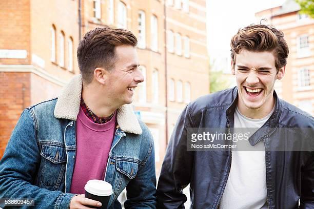 Junge Männer mit einem gut Lachen während der Fahrt zu Fuß