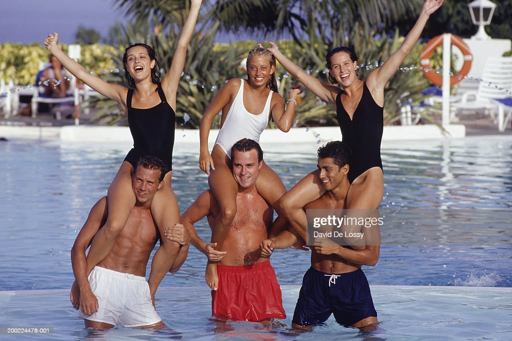 Young men holding young women on shoulders in pool : Stock Photo
