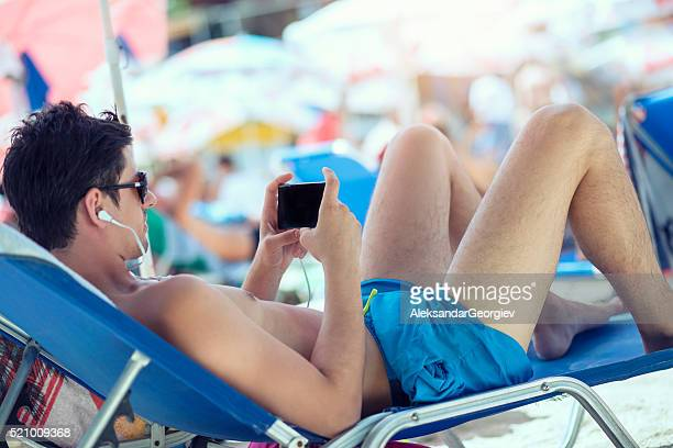 Young Men how Using Smartphone while Sunbathing on the Beach