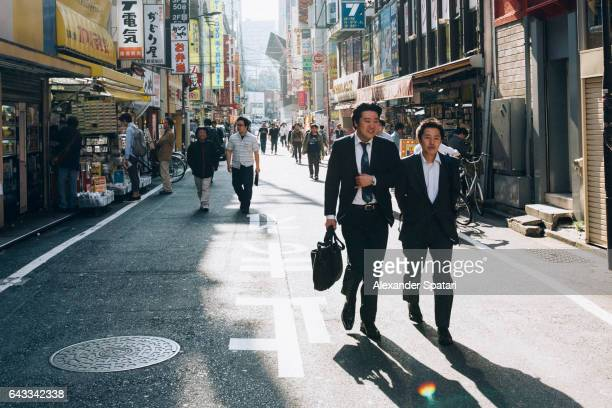 Young men in business suits walking at the streets of Akihabara, Tokyo, Japan