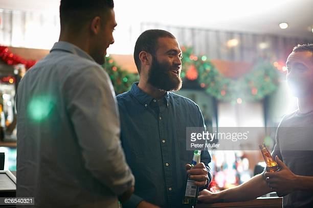 Young men in public house holding beer bottles leaning against counter smiling