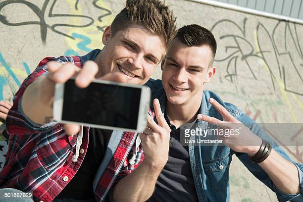 Young men in skatepark, taking self portrait photograph, using smartphone