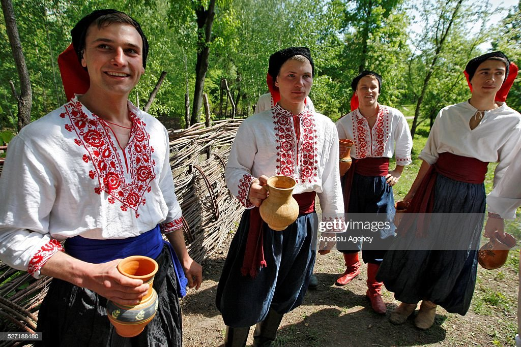 Young men in Ukrainian traditional clothes hold carafes filled with water and wait the women during folk Easter Tradition of pouring water called 'Pouring Monday' in open air Cossack village 'Mamaeva Sloboda', Ukraine,on May 02, 2016. The tradition of pouring water when single guys pour unmarried girls by water is celebrated on the first Monday after Orthodox Easter.