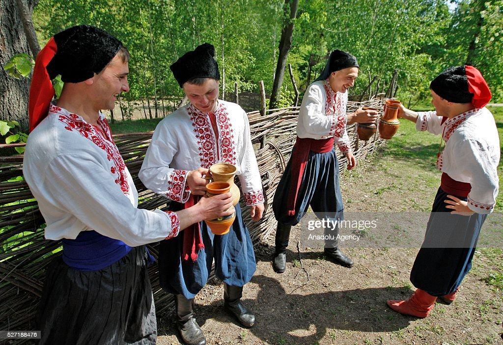 Young men in Ukrainian traditional clothes hold carafes with water during folk Easter Tradition of pouring water called 'Pouring Monday' in open air Cossack village 'Mamaeva Sloboda', Ukraine,on May 02, 2016. The tradition of pouring water when single guys pour unmarried girls by water is celebrated on the first Monday after Orthodox Easter.