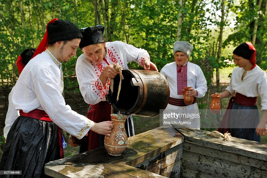 Young men in Ukrainian traditional clothes pour water from a well during folk Easter Tradition of pouring water called 'Pouring Monday' in open air Cossack village 'Mamaeva Sloboda', Ukraine,on May 02, 2016. The tradition of pouring water when single guys pour unmarried girls by water is celebrated on the first Monday after Orthodox Easter.