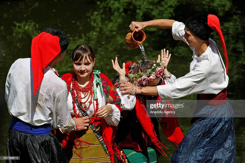 Young men in Ukrainian traditional clothes pour water on the women during folk Easter Tradition of pouring water called 'Pouring Monday' in open air Cossack village 'Mamaeva Sloboda', Ukraine,on May 02, 2016. The tradition of pouring water when single guys pour unmarried girls by water is celebrated on the first Monday after Orthodox Easter.
