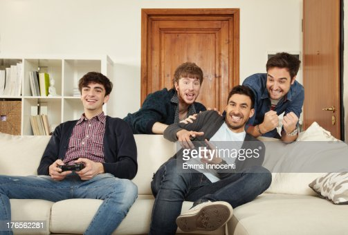 Young men indoors playing video games