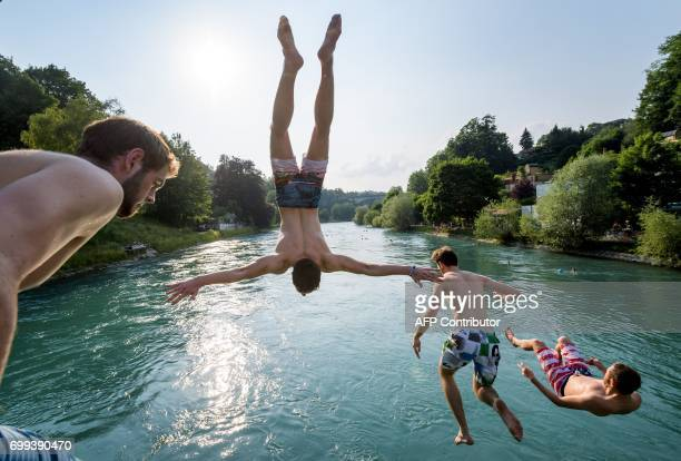 TOPSHOT Young men jump into the river Aare on June 21 2017 in Bern Europe sizzled in a continentwide heatwave with London bracing for Britain's...
