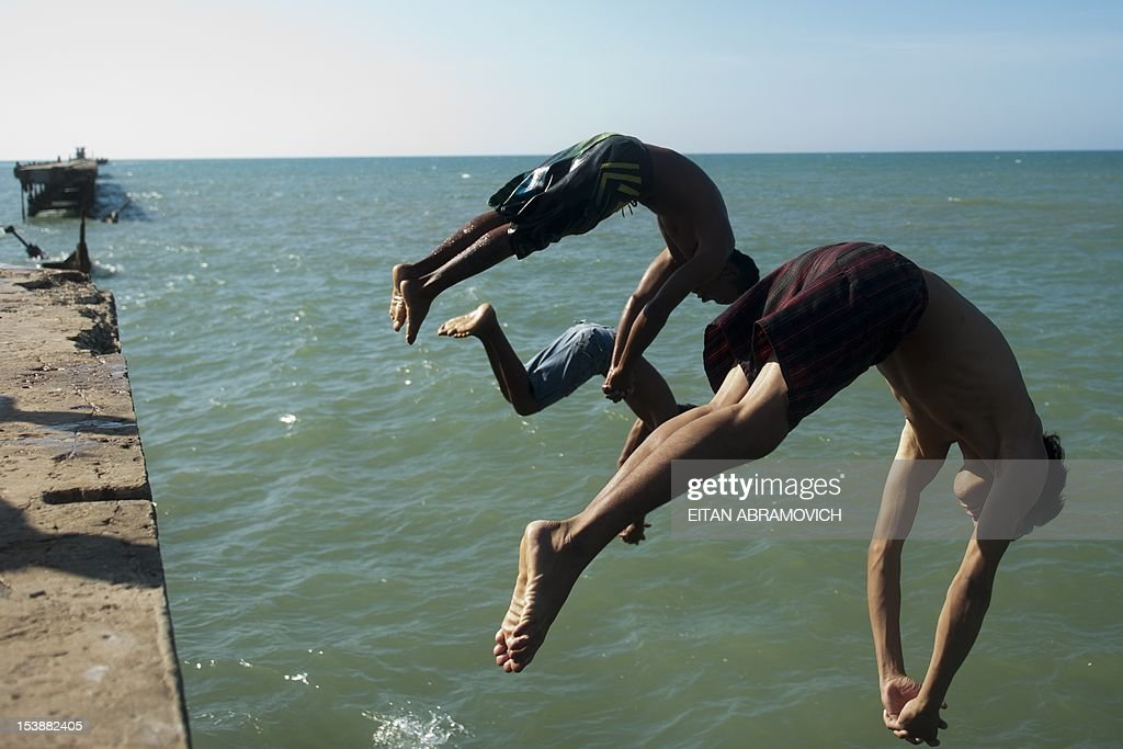 Young men jump into the sea at the pier of Puerto Colombia, Atlantico department, Colombia on October 10, 2012. Between 1893 and 1936 the pier worked as Barranquilla sea terminal for loading and unloading of goods and people, and after the separation of Panama from Colombia until the decade of 1920 it was considered the most important seaport in Colombia. AFP PHOTO/Eitan Abramovich