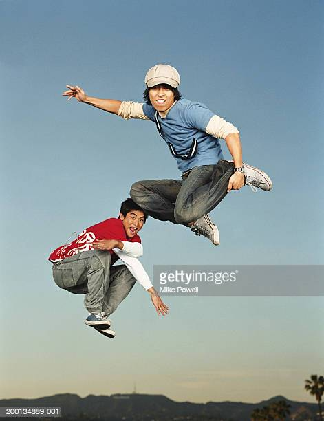 Young men jumping in air, portrait, low angle