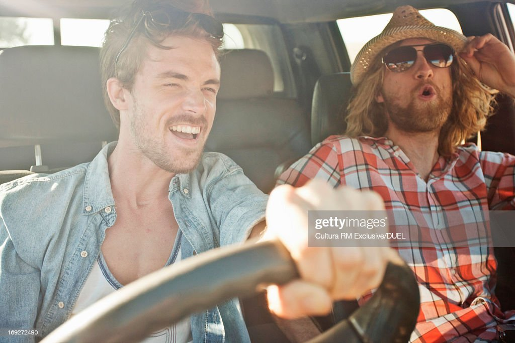 Young men laughing and driving in car on road trip : Stock Photo