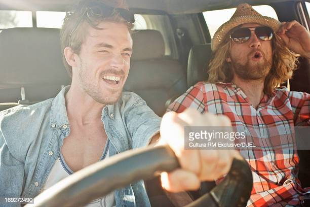 Young men laughing and driving in car on road trip