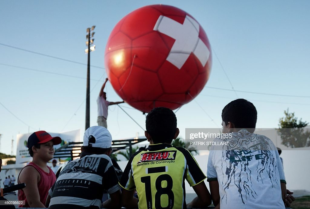 Young men look at a man pumping up a huge ballon bearing the colours of the Swiss flag during a training session of Switzerland's national football team in Porto Seguro, Brazil, on June 7, 2014, a few days before the start of the 2014 FIFA World Cup .