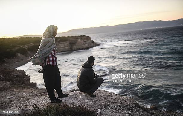 Young men look towards the Greek Chios island as they wait for the wind to calm down to travel on a dinghy with other migrants and refugees from...
