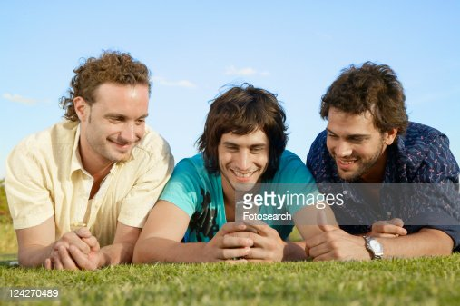 Young men looking at cell phone on grass
