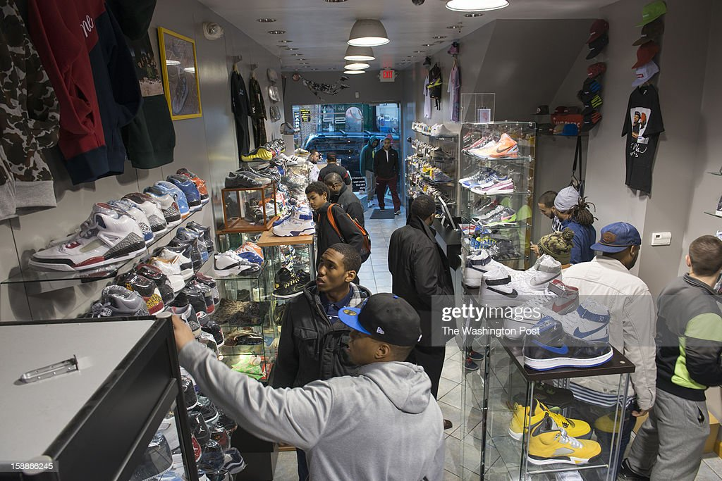Young men pause and examine hundreds of pairs of popular sneakers crowd the Kickk Spott store in Washington, D.C. on December 28, 2012. Kickk Spott is the only ultra-high end sneaker shop in the area, and the only one that does consignment as well.