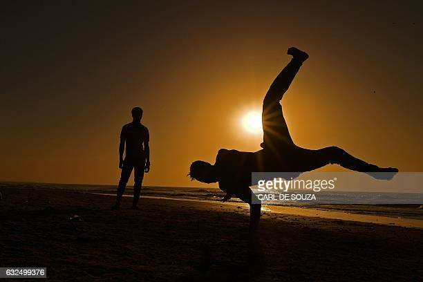 Young men perform acrobatics on the beach in Serekunda outside Banjul on January 23 2017 The beaches and hotels in Gambia remain almost empty...