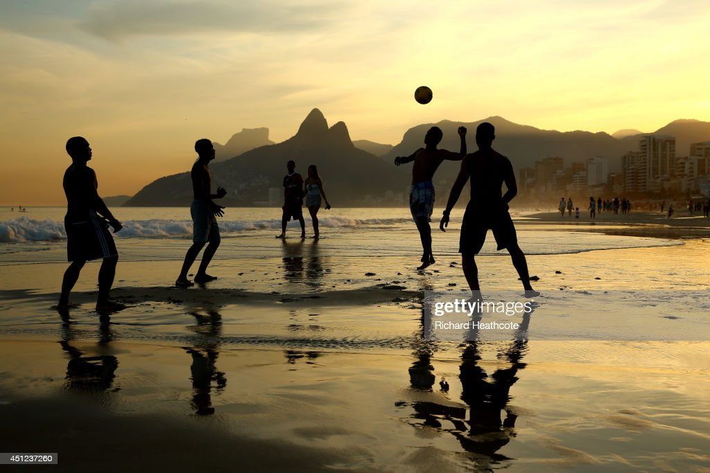 Young men play beach football as the sunsets on Ipanema beach on June 25, 2014 in Rio de Janeiro, Brazil.