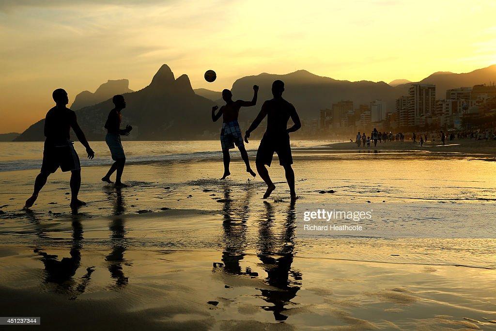 Young men play beach football as the sunsets on Ipanema beach on June 25 2014 in Rio de Janeiro Brazil