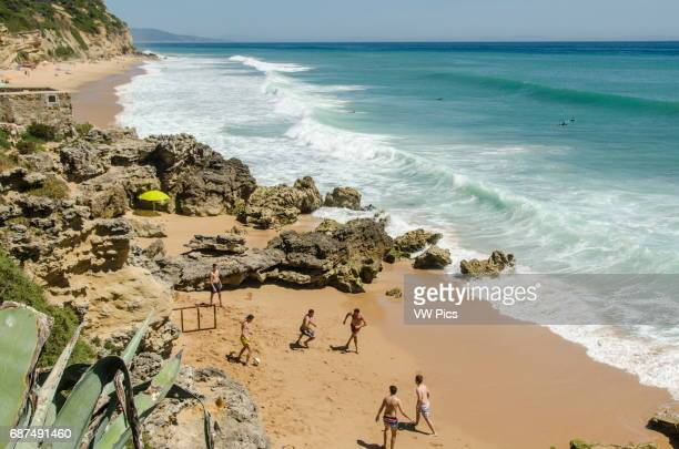 Young men play football on a beach in the small seaside town of Los CaÐos de Meca in Càdiz Province Some surfers wait for waves and the coastline...
