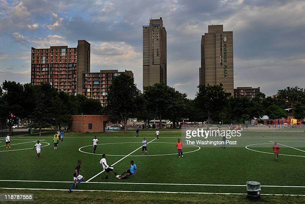 Young men play soccer as mothers and fathers socialize and parent their playing children in Currie Park next to the CedarRiverside apartment complex...