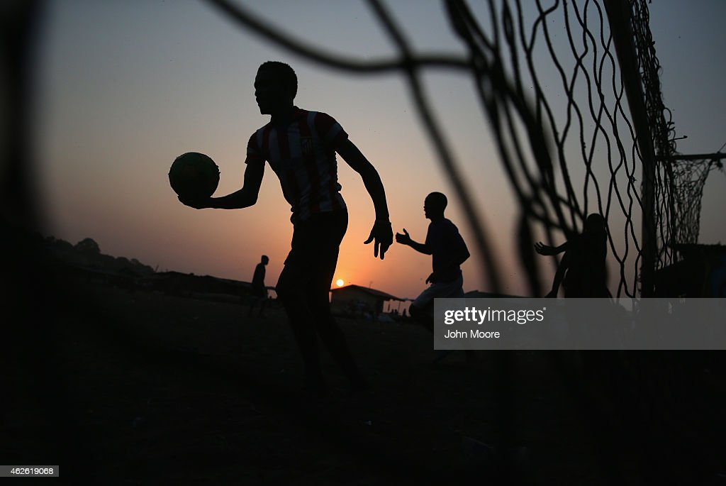 Young men play soccer at sunset in the West Point township on January 31 2015 in Monrovia Liberia Life has slowly begun to return to normal for many...
