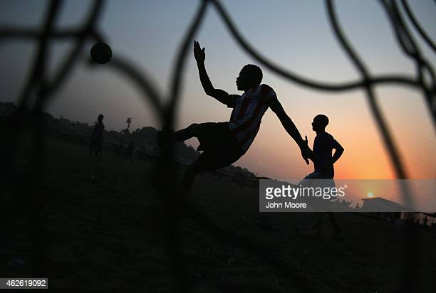 Young men play soccer at sunset in the West Point township on January 31 2015 in Monrovia Liberia Life has begun to slowly return to normal for many...