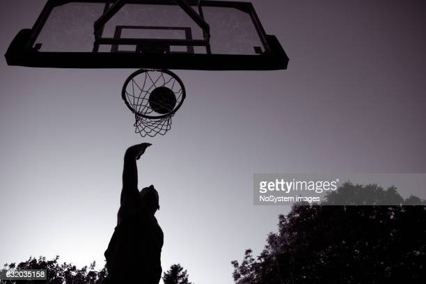Young men playing basketball on outdoor court