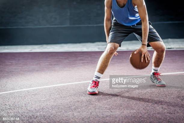 Young men playing basketball on outdoors court
