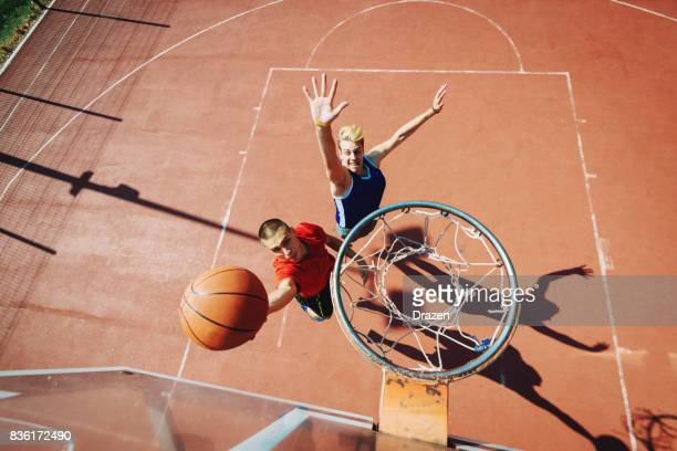 Young men playing basketball one on one