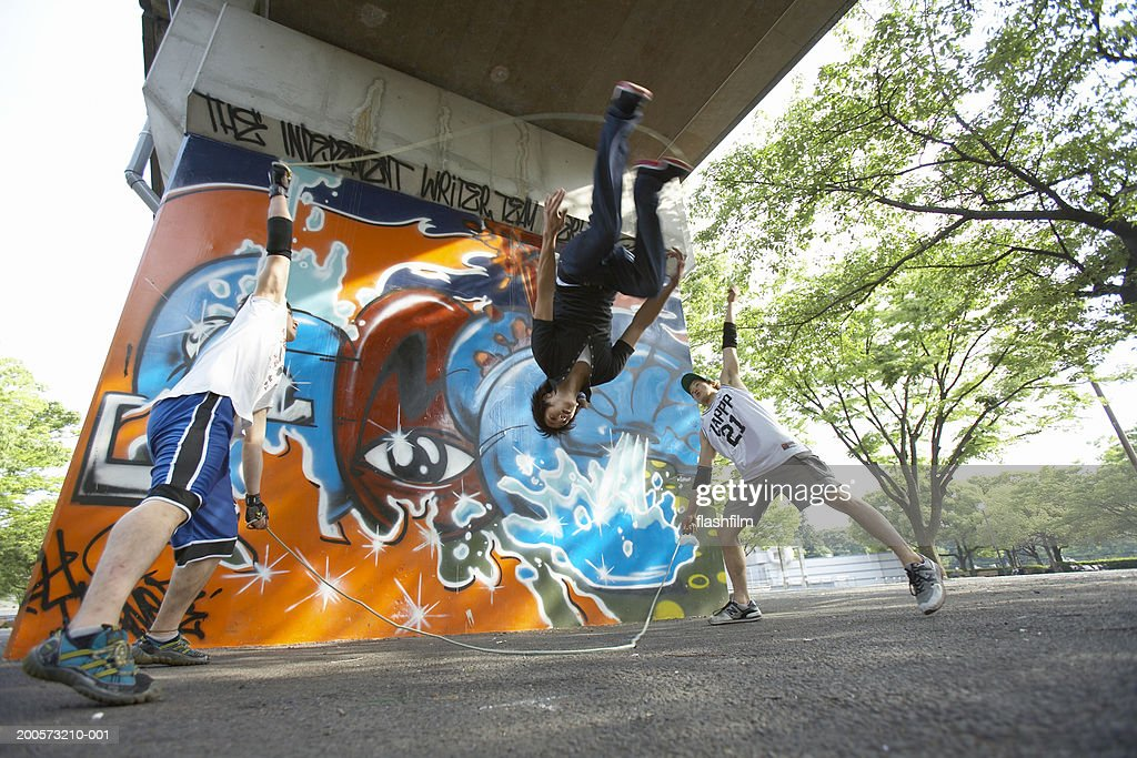 Young men playing double dutch, low angle view : Stock Photo