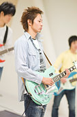 Young men playing electric guitar, differential focus