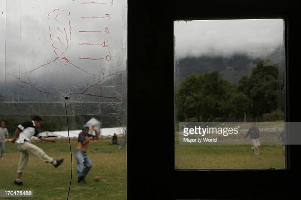 Young men playing football near a shelter for the volcanic eruption survivors The Tungurahua an active volcano in the Cordillera Central of Ecuador...