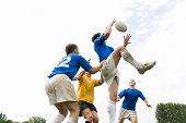 Young men playing rugby, jumping into air to catch ball, low angle view