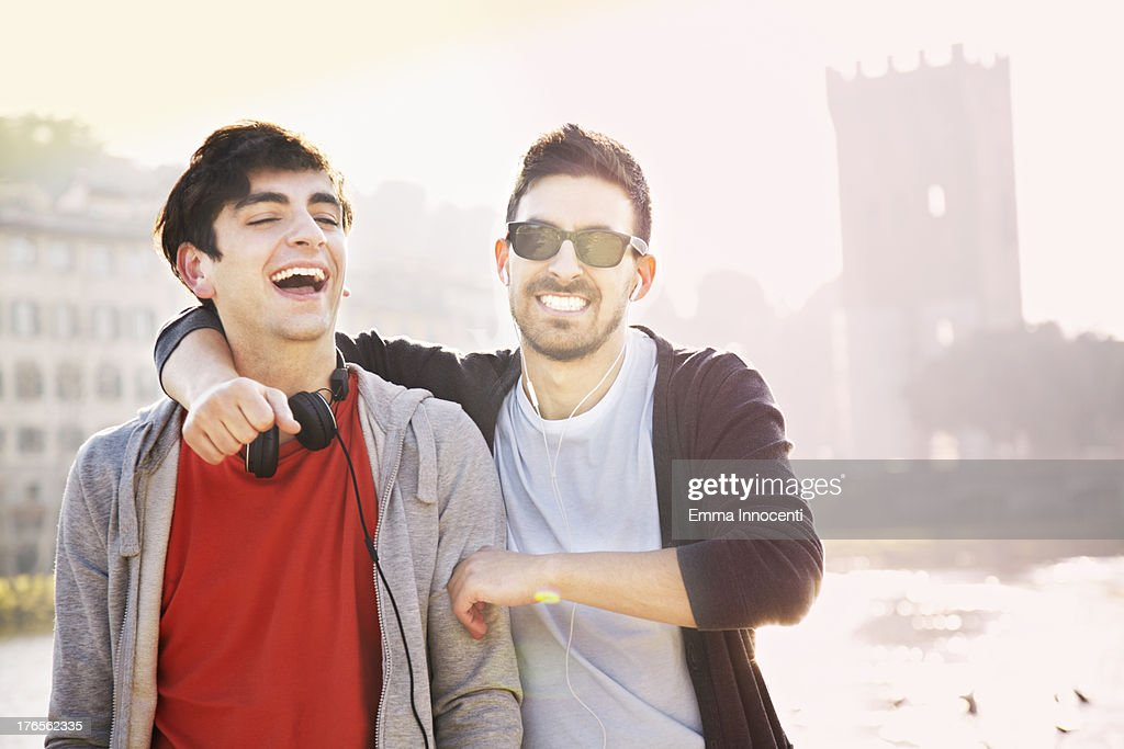 Young men, playing, sunset, river bank, city